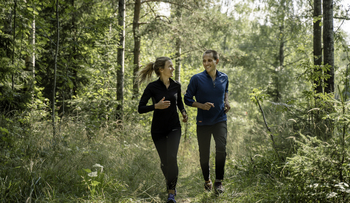 Ungt par løper i skogen